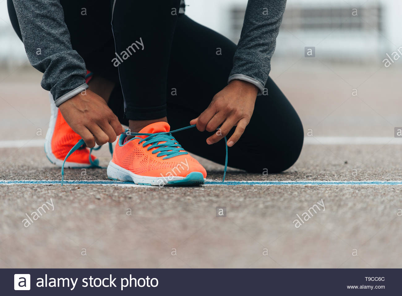 Detail of sporty swman lacing running shoes before before training. Outdoor city workout concept. Female fitness athlete getting ready for working out Stock Photo