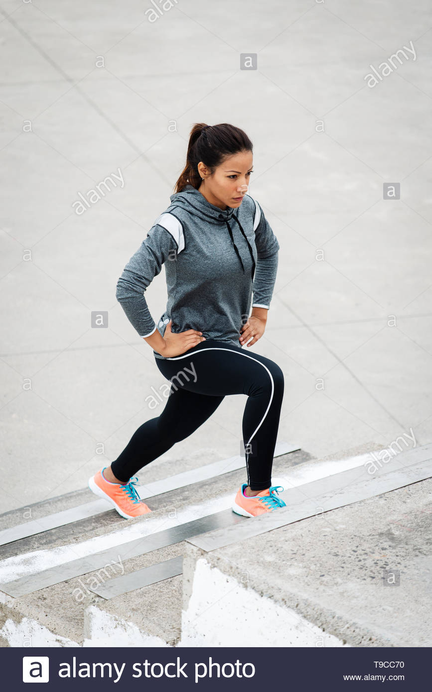 Leg lunges exercise on stairs. Fitness woman working out in the city. - Stock Image
