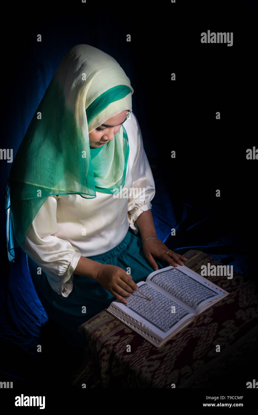 FLORES, INDONESIA-JUNE 25 2014: A teenage girl around 15-20 years old wearing a hijab is reading the quran on a table with ethnic motifs to welcome th - Stock Image