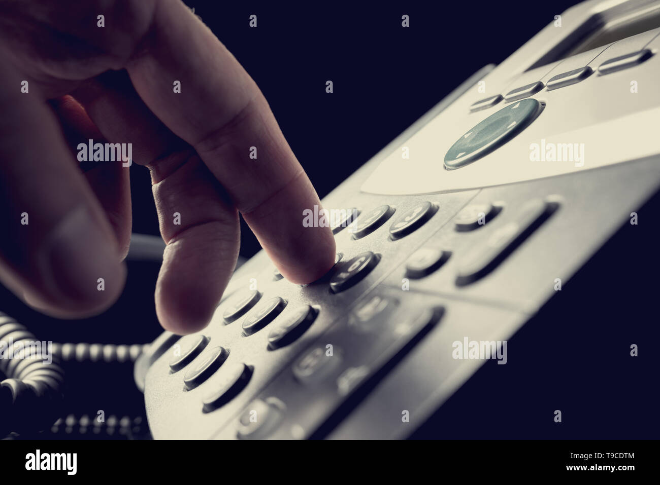 Person dialing out on a telephone punching in the numbers on the keypad with a finger, vintage effect toned image. - Stock Image