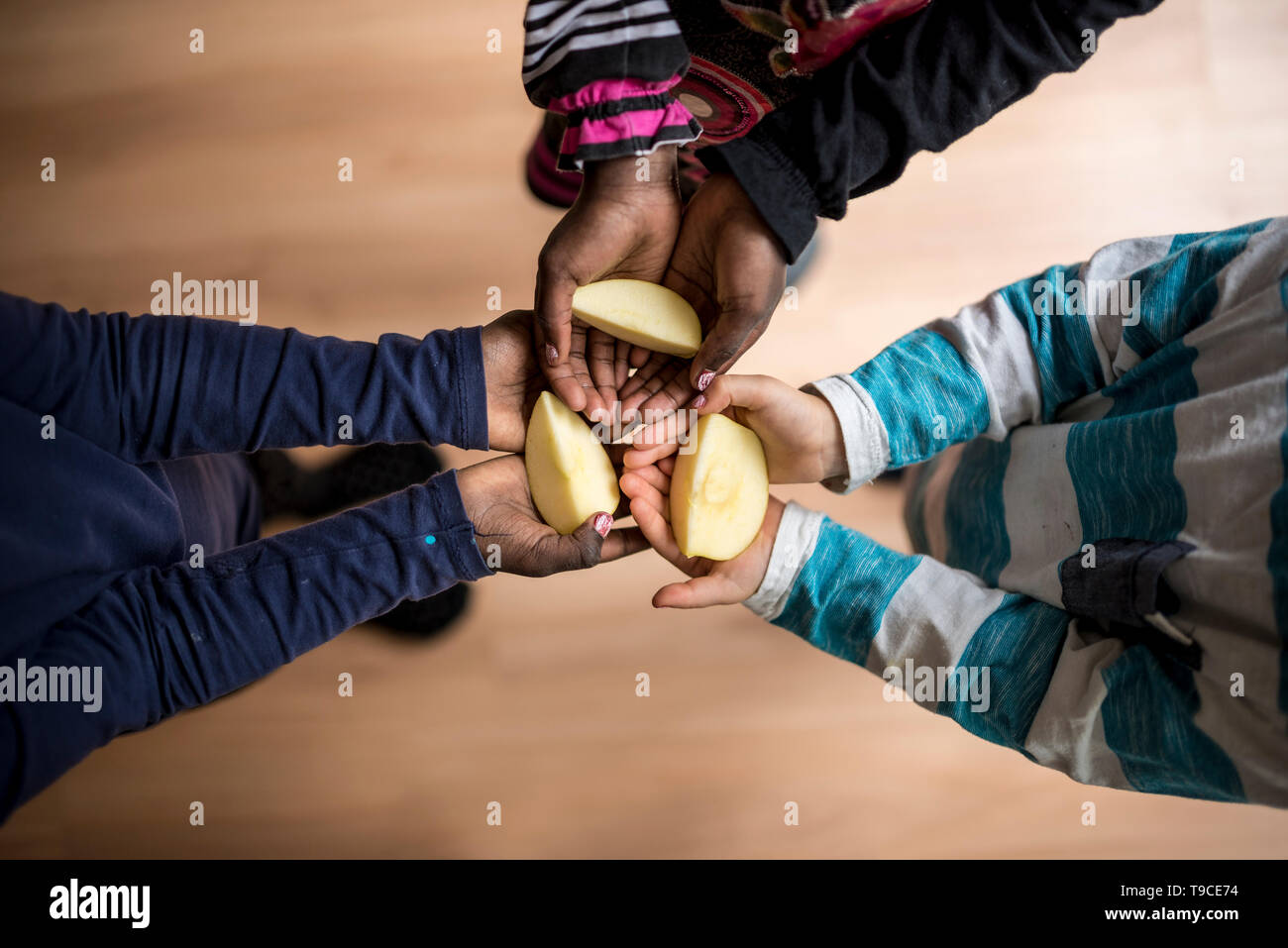 Top view of three kids of mixed races each holding a piece of apple in the palms of their hands. - Stock Image