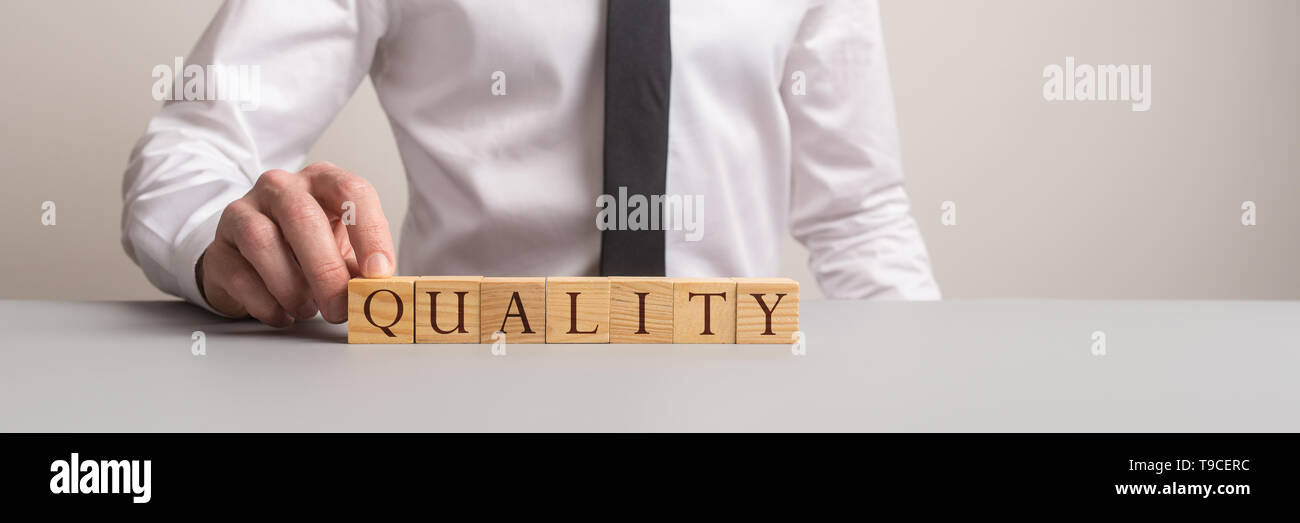Wide view image of businessman making a Quality sign of wooden blocks in a conceptual image of top business service. - Stock Image