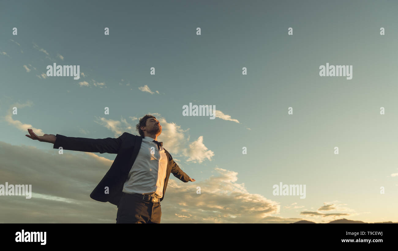 View from below of a young businessman in a suit enjoying his freedom and professional independence with arms wide open standing under evening sky. - Stock Image
