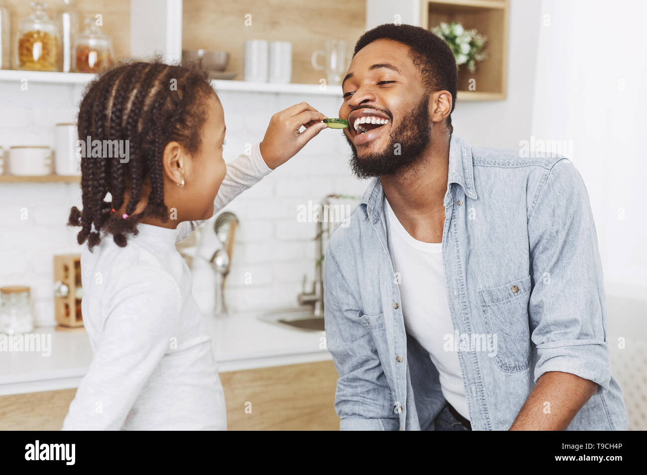 Young daughter is feeding her father with chocolate cookies - Stock Image