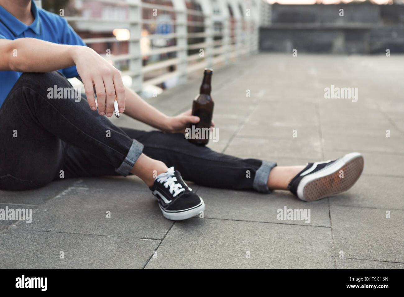 Teen guy smoking cigarette and drinking beer, sitting alone - Stock Image