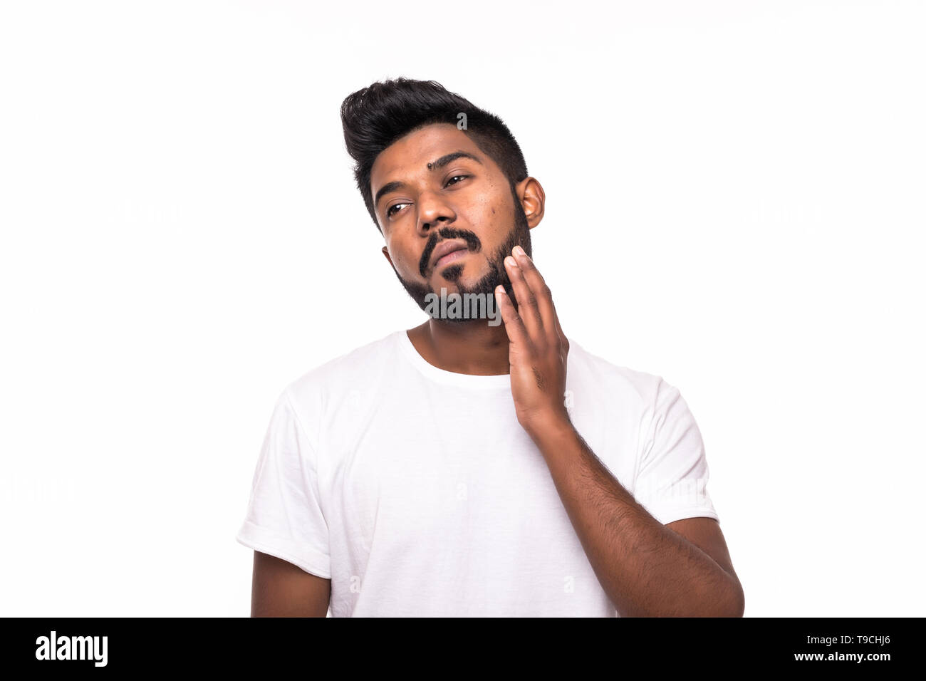 Attractive young indian man touch his beard on white background - Stock Image