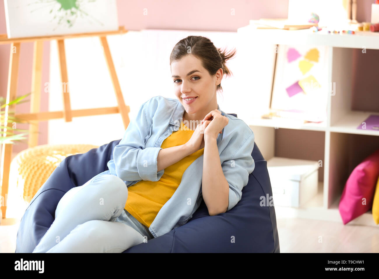 Young female painter sitting on beanbag chair in studio - Stock Image