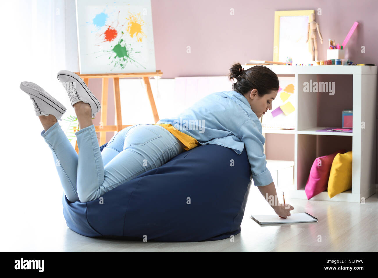 Young female painter on beanbag chair in studio - Stock Image