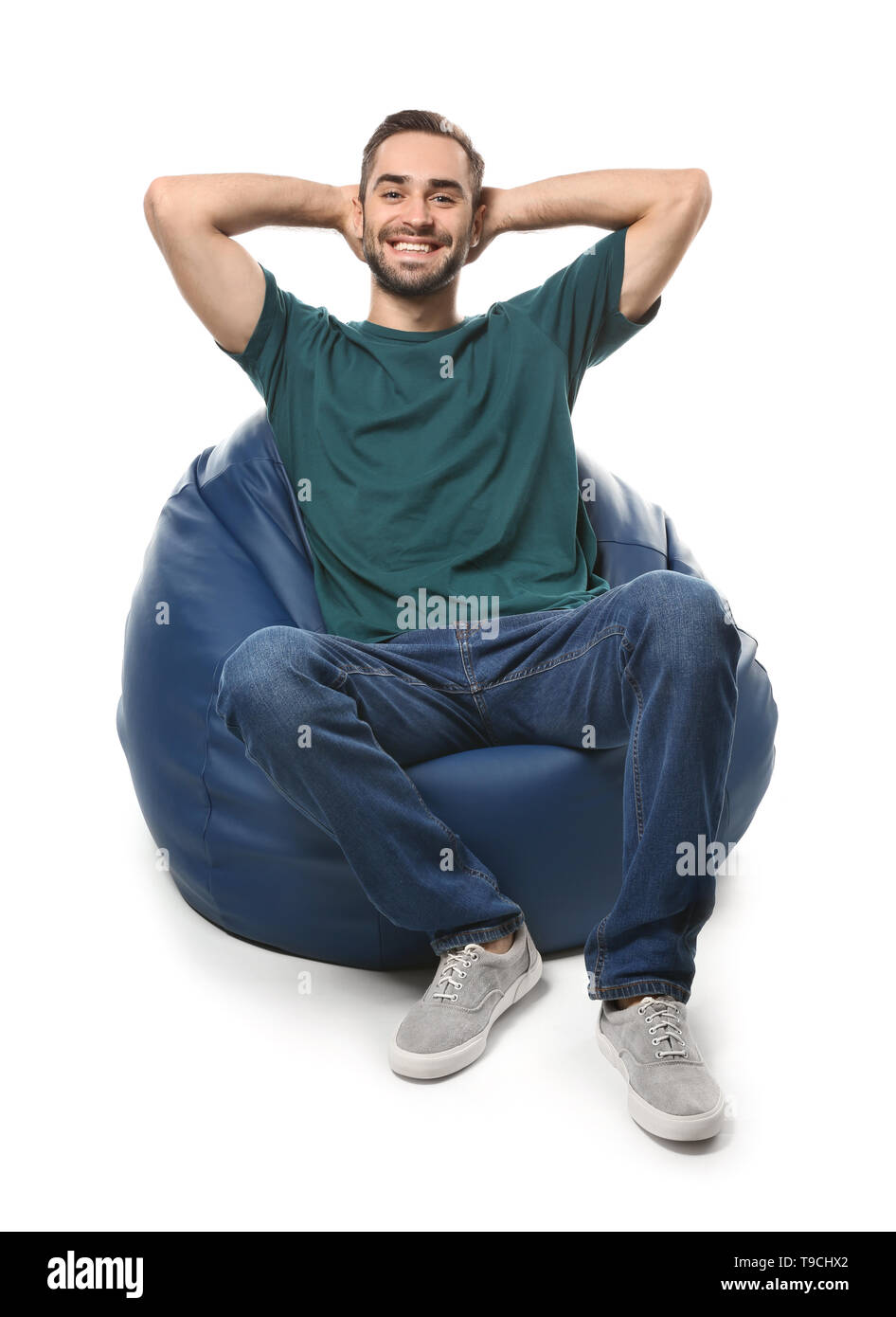 Young man sitting on beanbag chair against white background - Stock Image