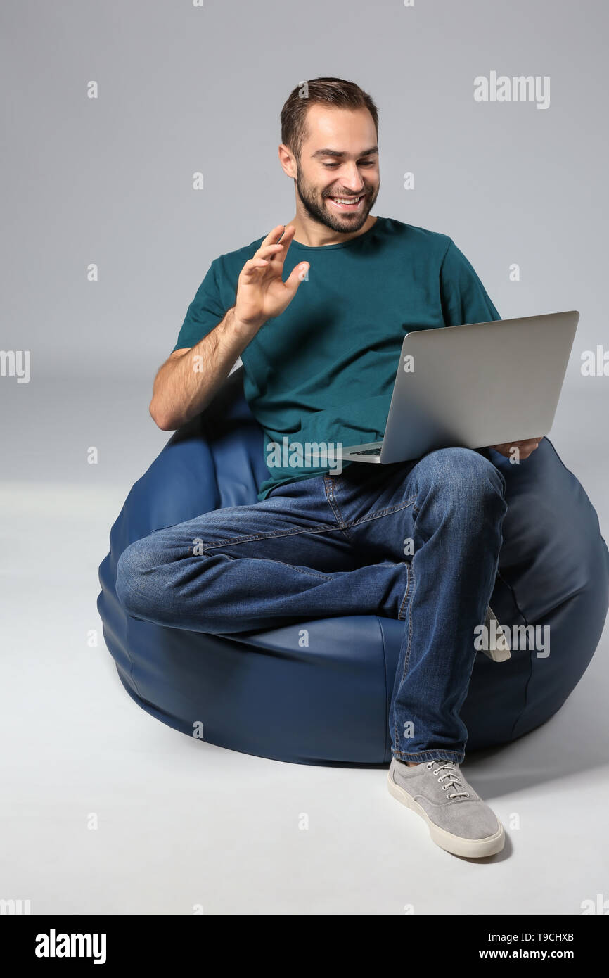 Young man with laptop sitting on beanbag chair against grey background - Stock Image
