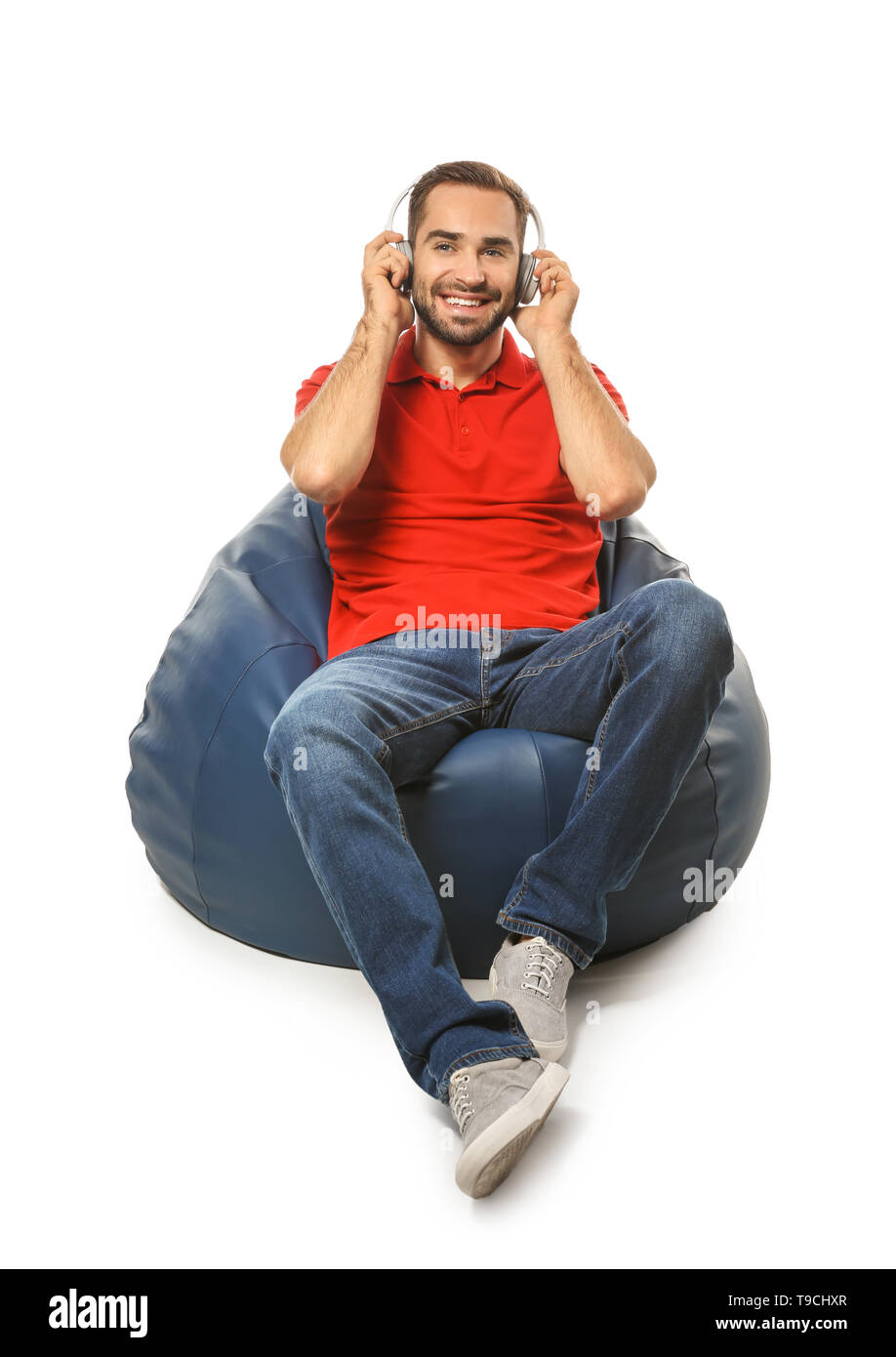 Young man with headphones sitting on beanbag chair against white background - Stock Image
