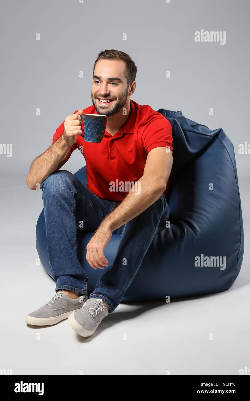 Young man with cup of tea sitting on beanbag chair against grey background - Stock Image