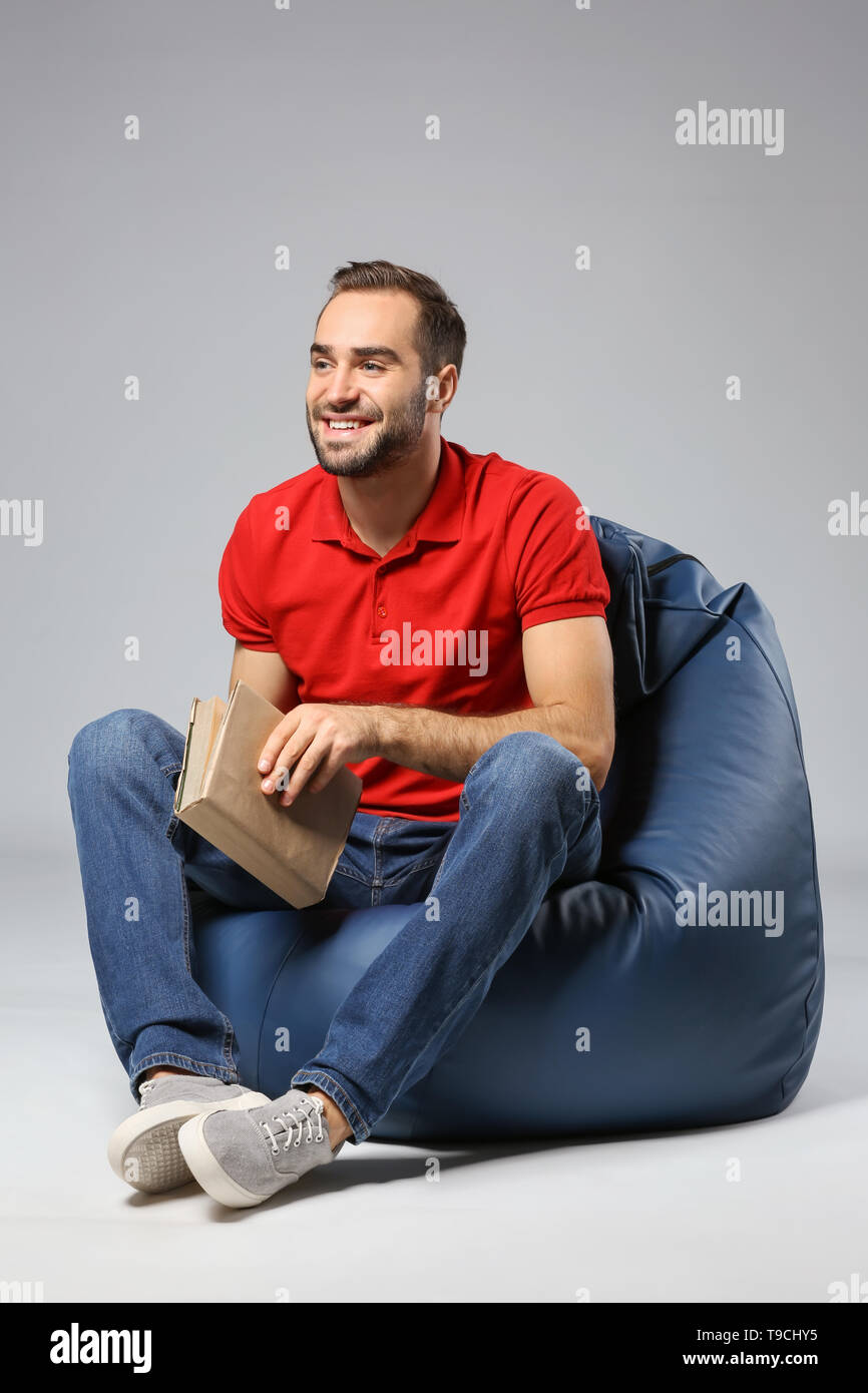 Young man with book sitting on beanbag chair against grey background - Stock Image