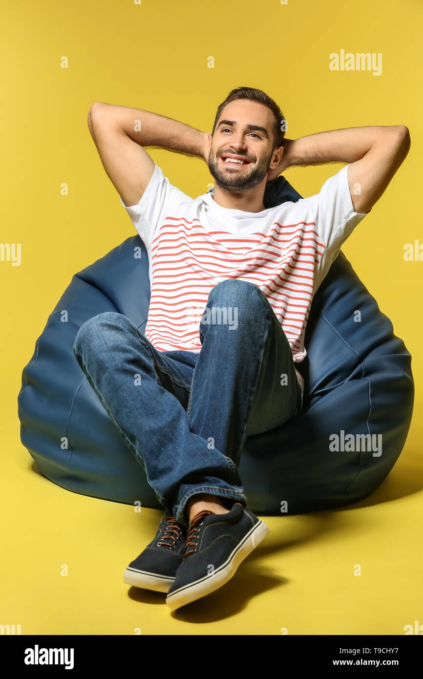 Young man sitting on beanbag chair against color background - Stock Image