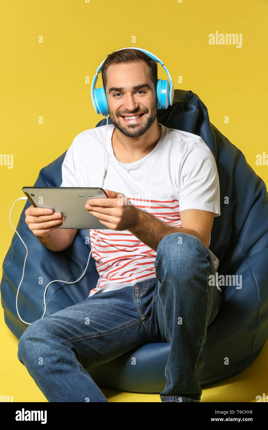 Young man with tablet PC and headphones sitting on beanbag chair against color background - Stock Image