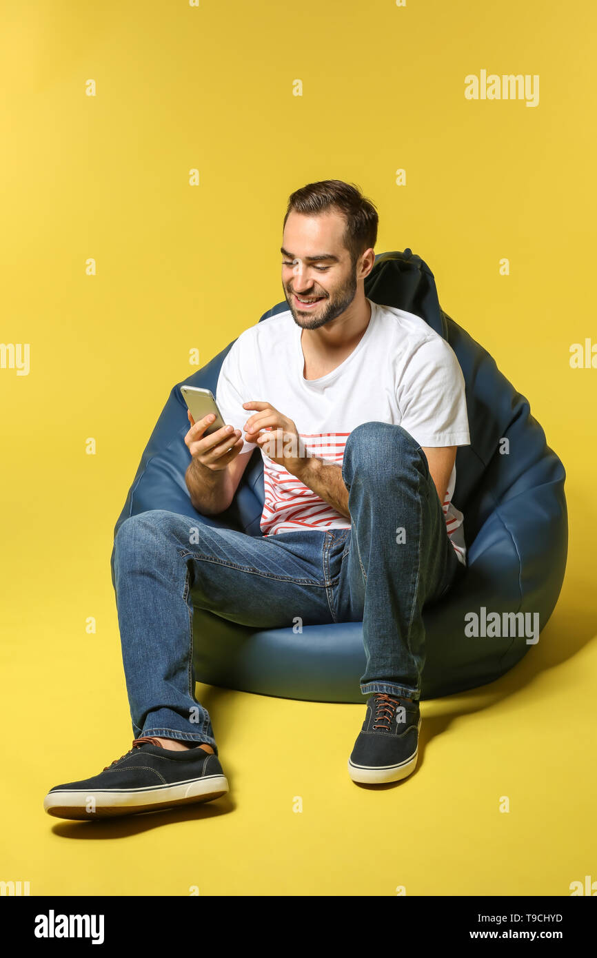 Young man with mobile phone sitting on beanbag chair against color background - Stock Image