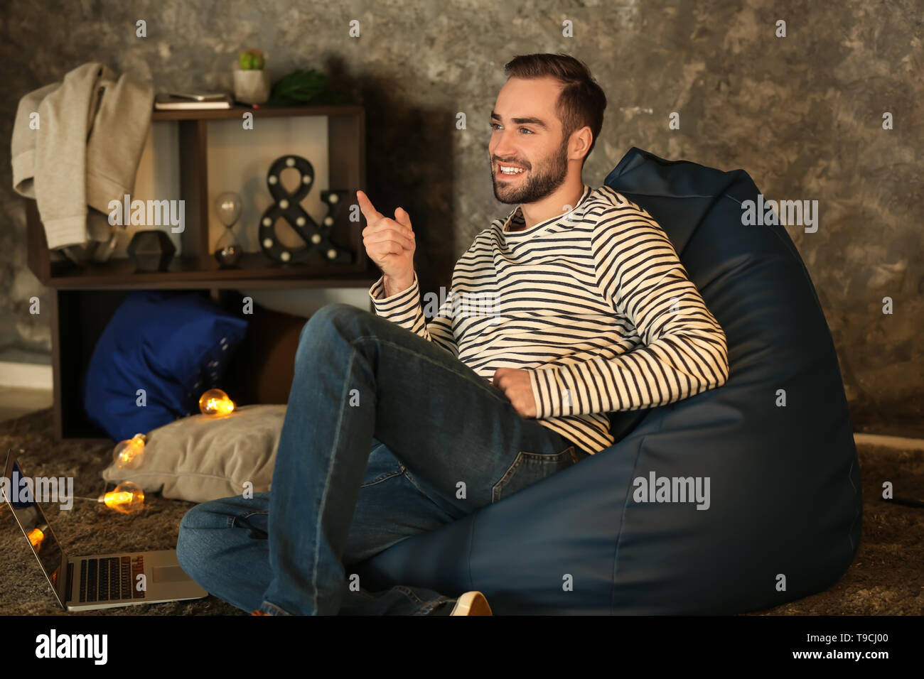 Young man sitting on beanbag chair at home - Stock Image