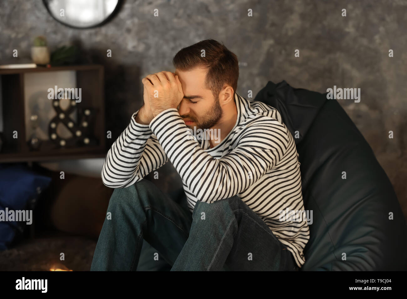 Tired man sitting at home in evening - Stock Image