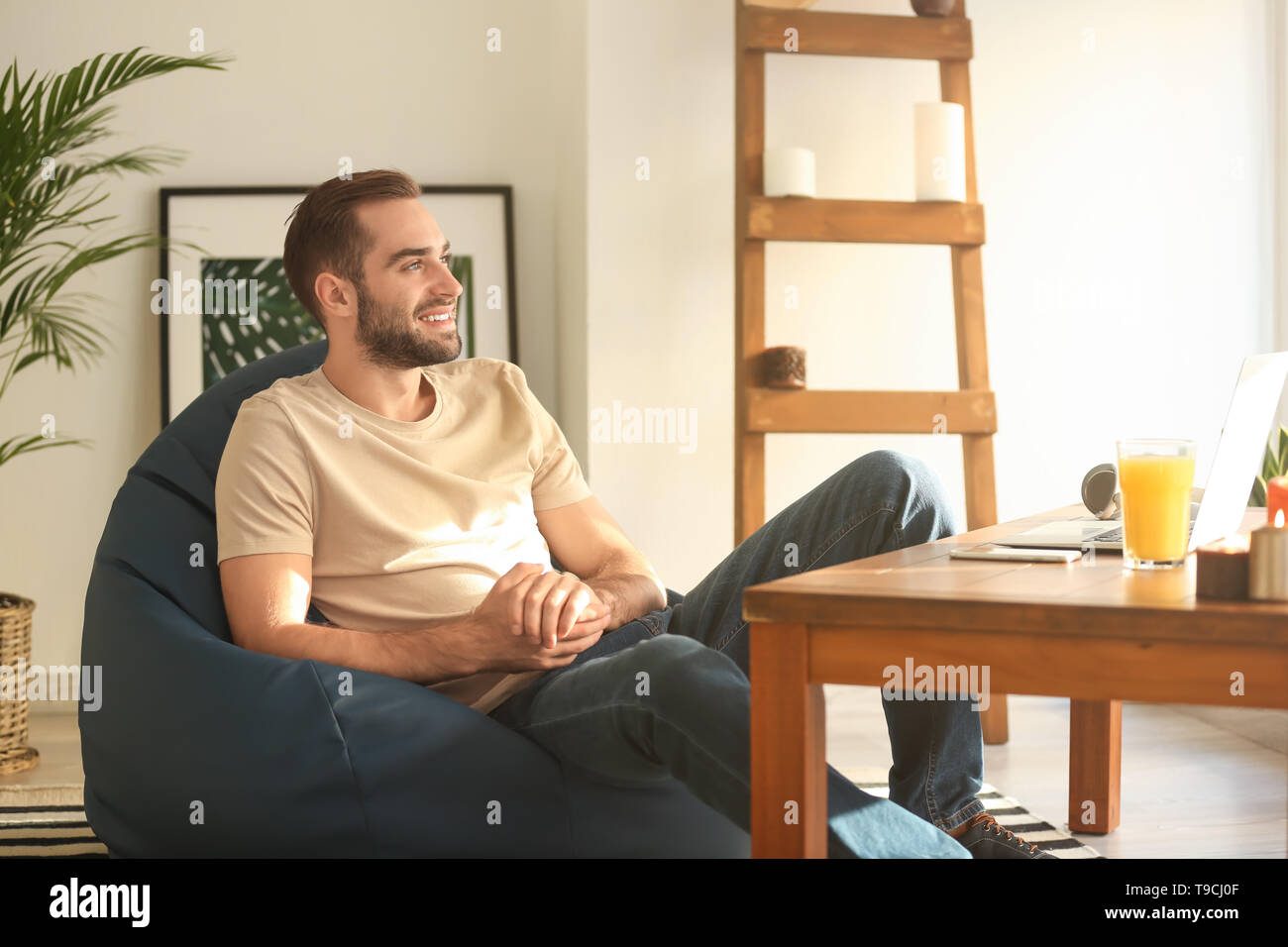 Fantastic Young Man Sitting On Beanbag Chair At Home Stock Photo Pabps2019 Chair Design Images Pabps2019Com