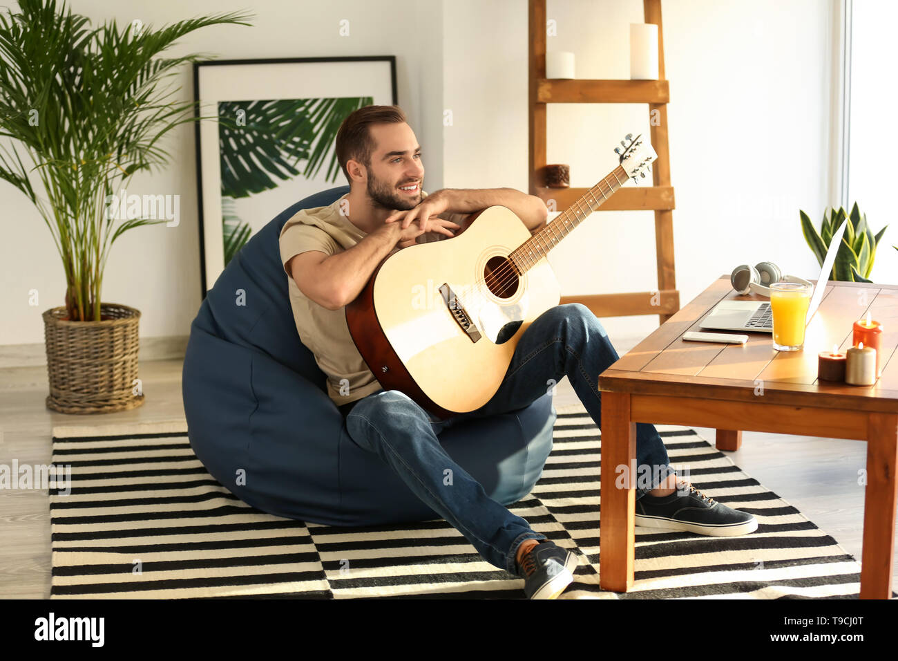 Young man with guitar sitting on beanbag chair at home - Stock Image