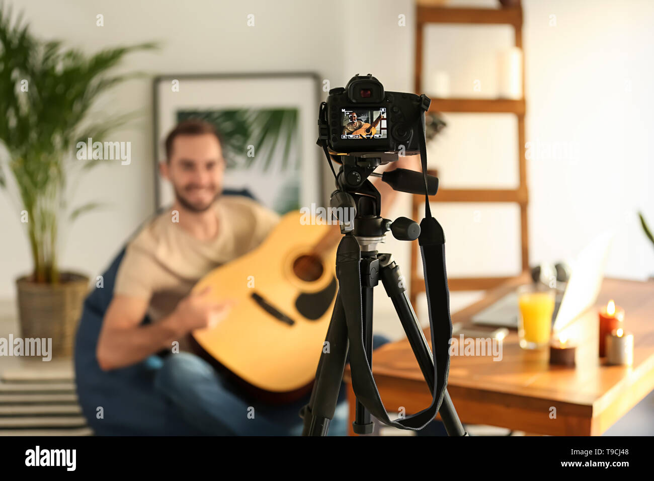 Young man with guitar recording video at home - Stock Image