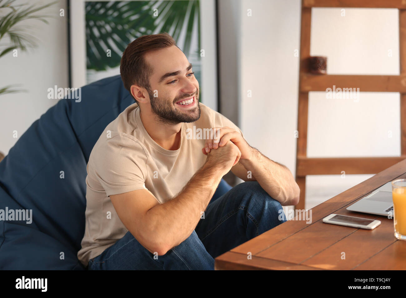 Happy young man at home - Stock Image
