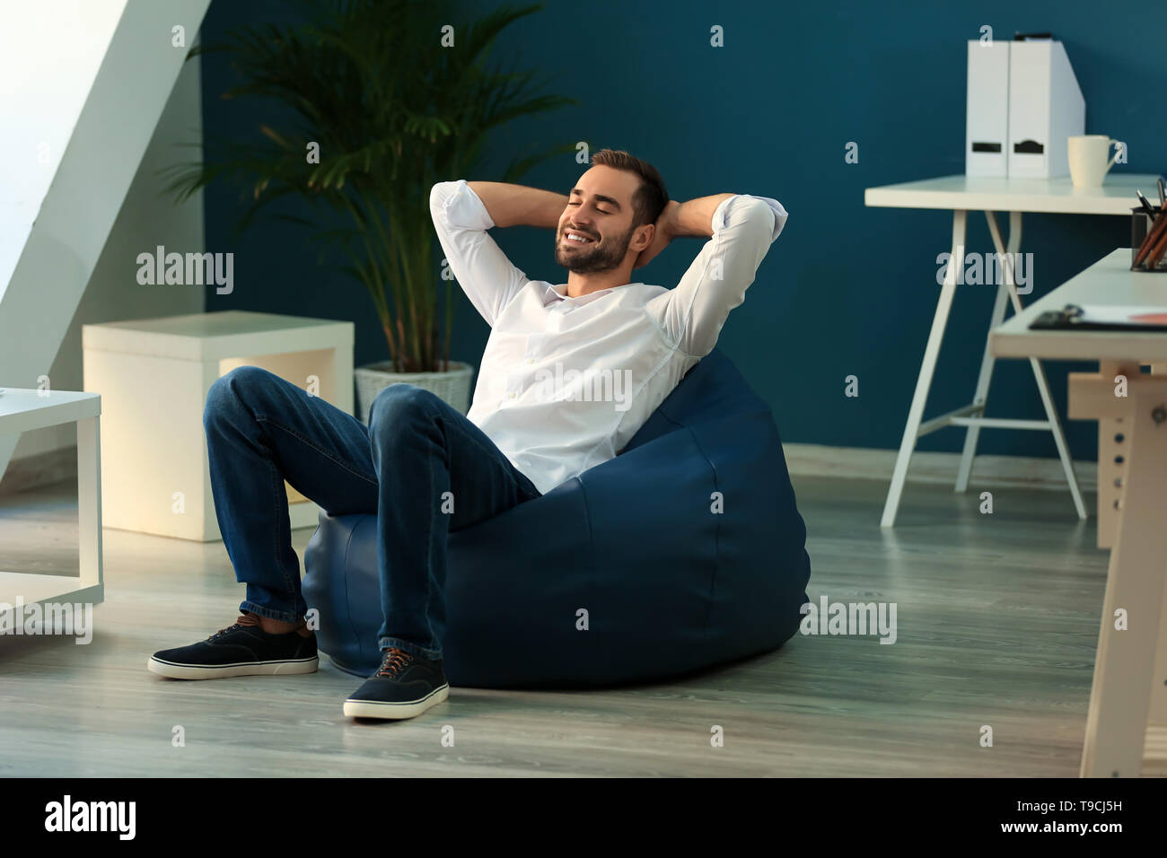 Young businessman sitting on beanbag chair in office - Stock Image