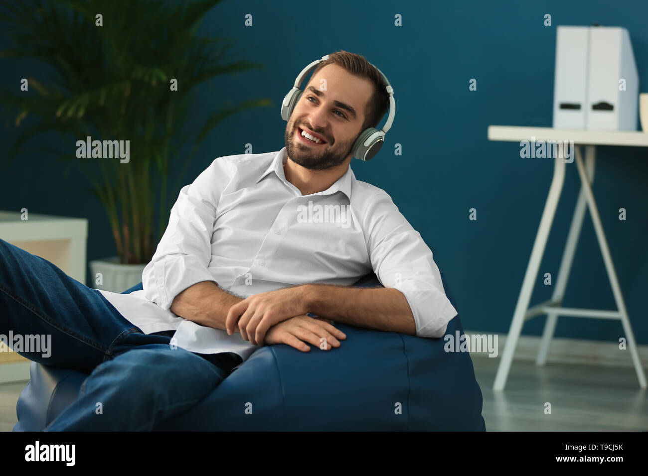 Young businessman with headphones sitting on beanbag chair in office - Stock Image