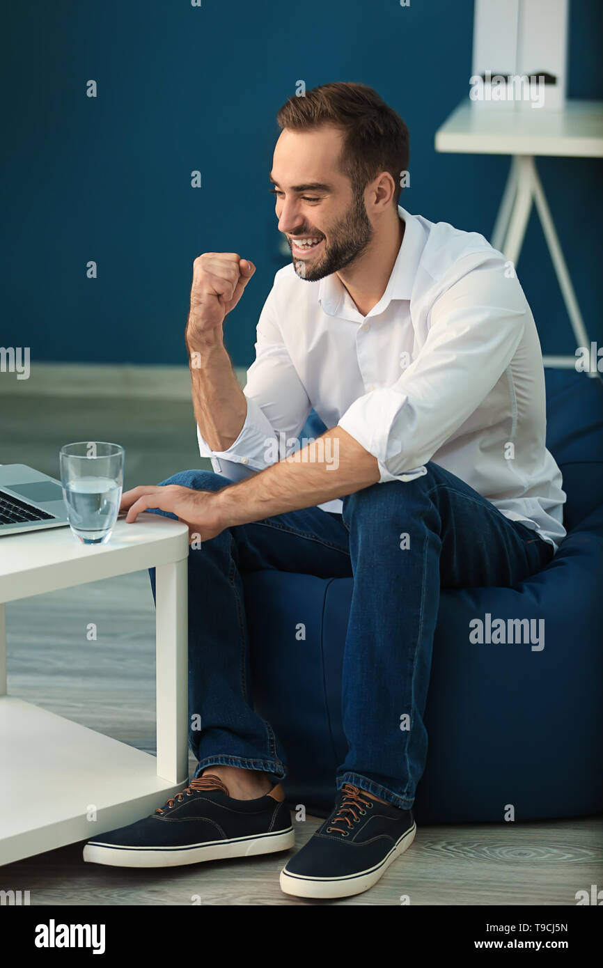 Young businessman with laptop working in office - Stock Image