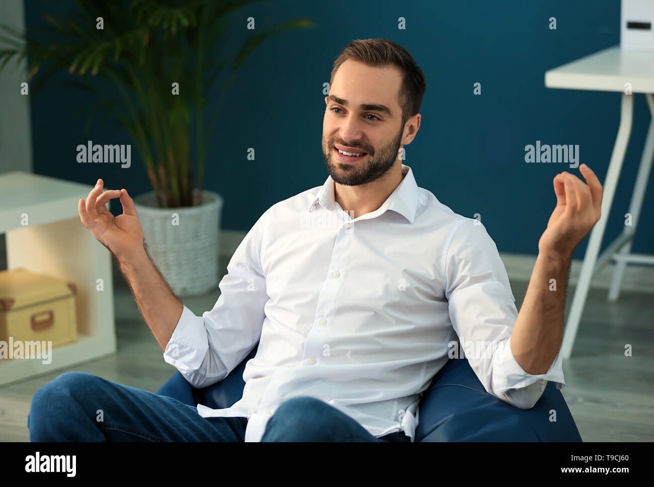 Young businessman meditating on beanbag chair in office - Stock Image