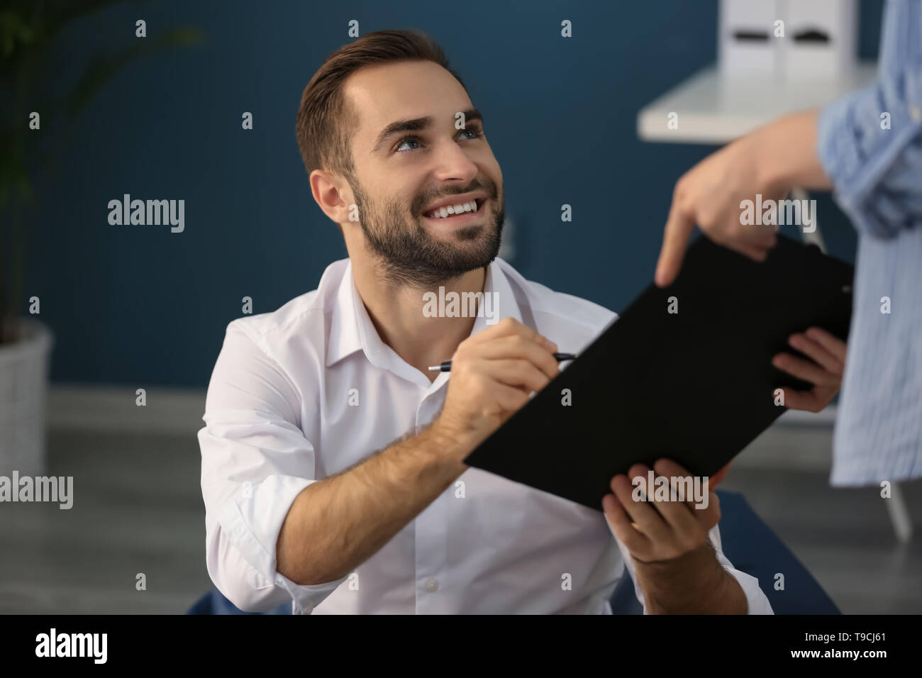 Young businessman working in office - Stock Image