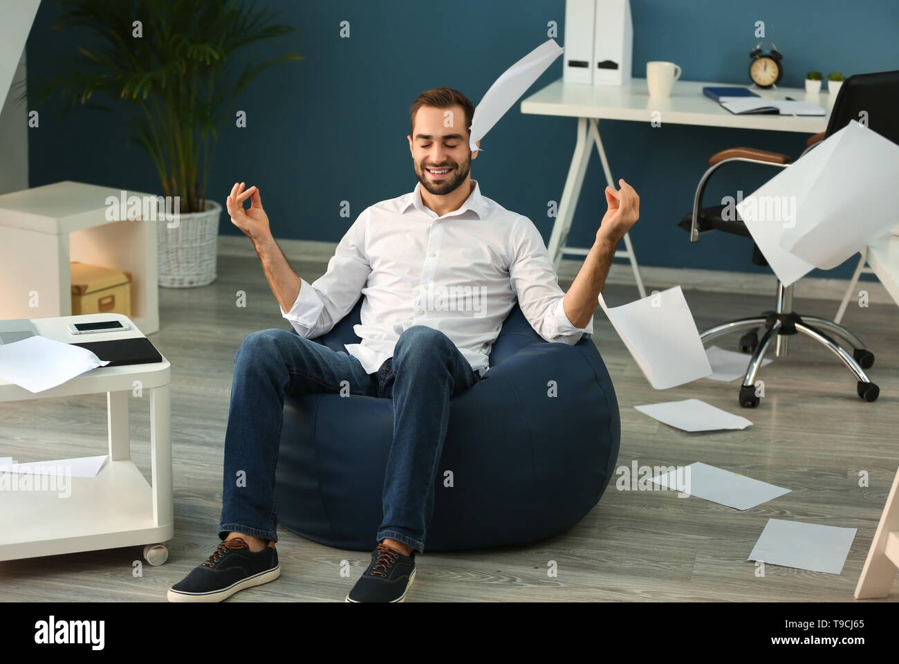 Businessman meditating with a lot of work in office - Stock Image
