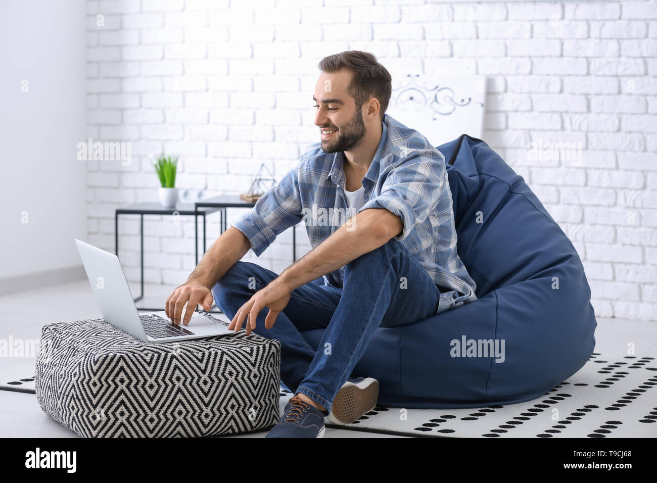 Young man with laptop sitting on beanbag chair at home - Stock Image