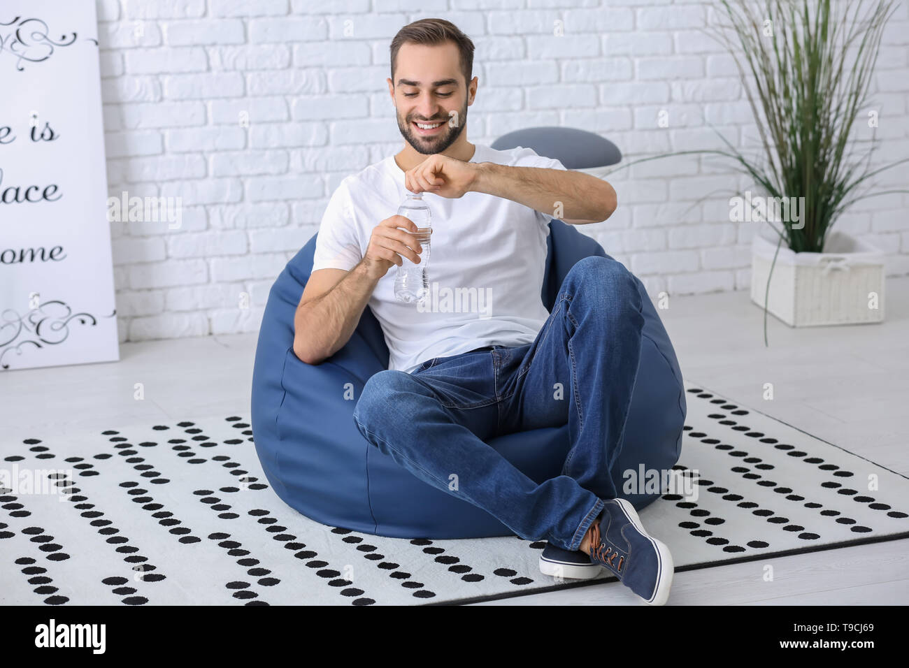 Young man with bottle of water sitting on beanbag chair at home - Stock Image