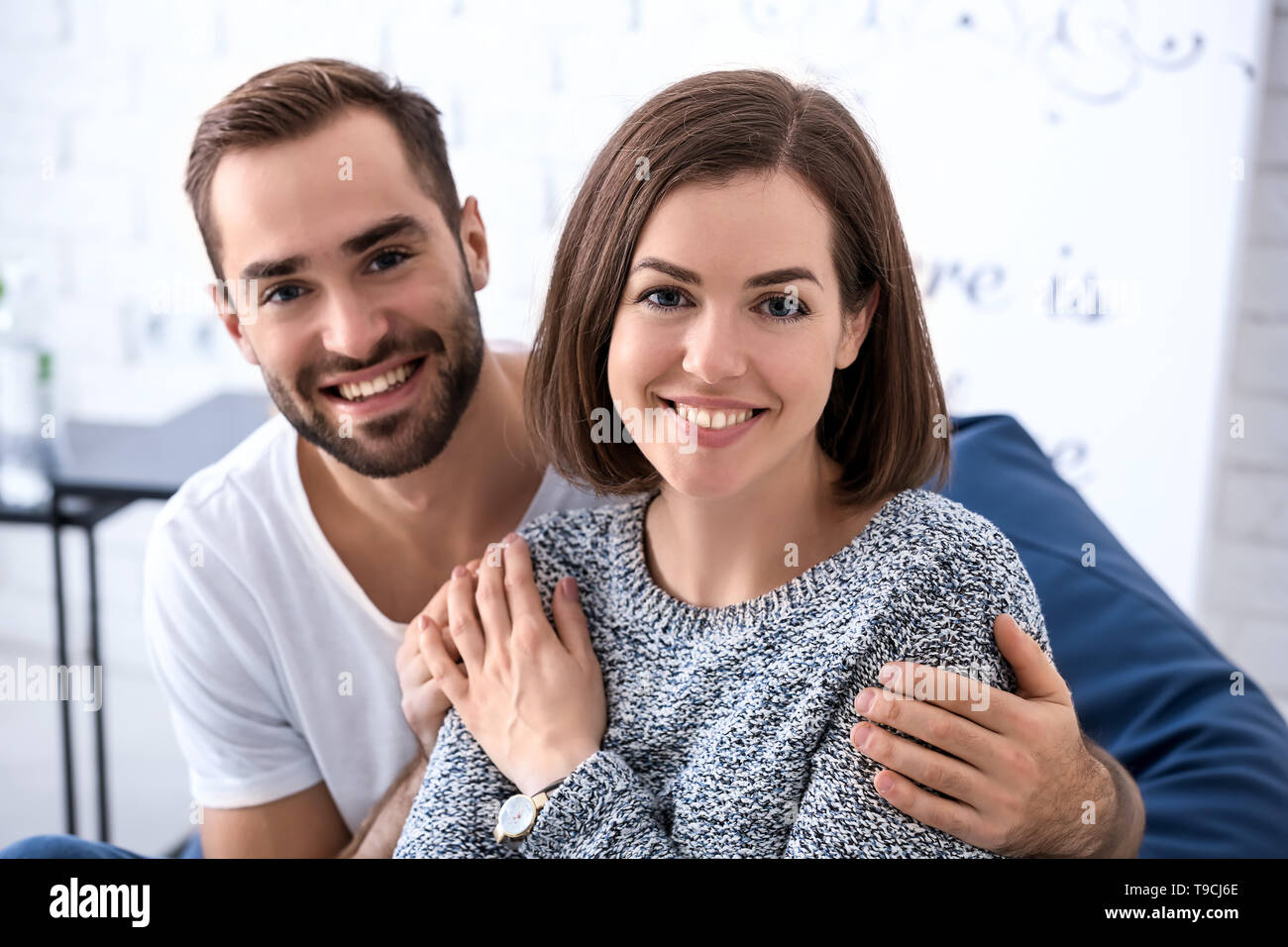 Portrait of happy young couple at home - Stock Image