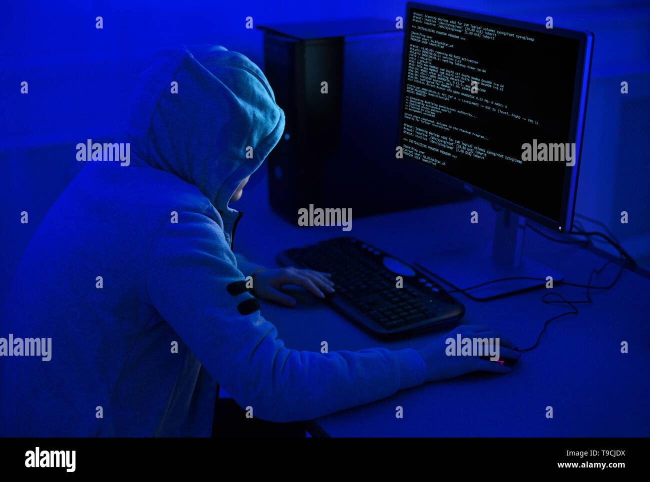 Cybercrime and Hacking Concept. Hacker Using Computer Virus Program - Stock Image