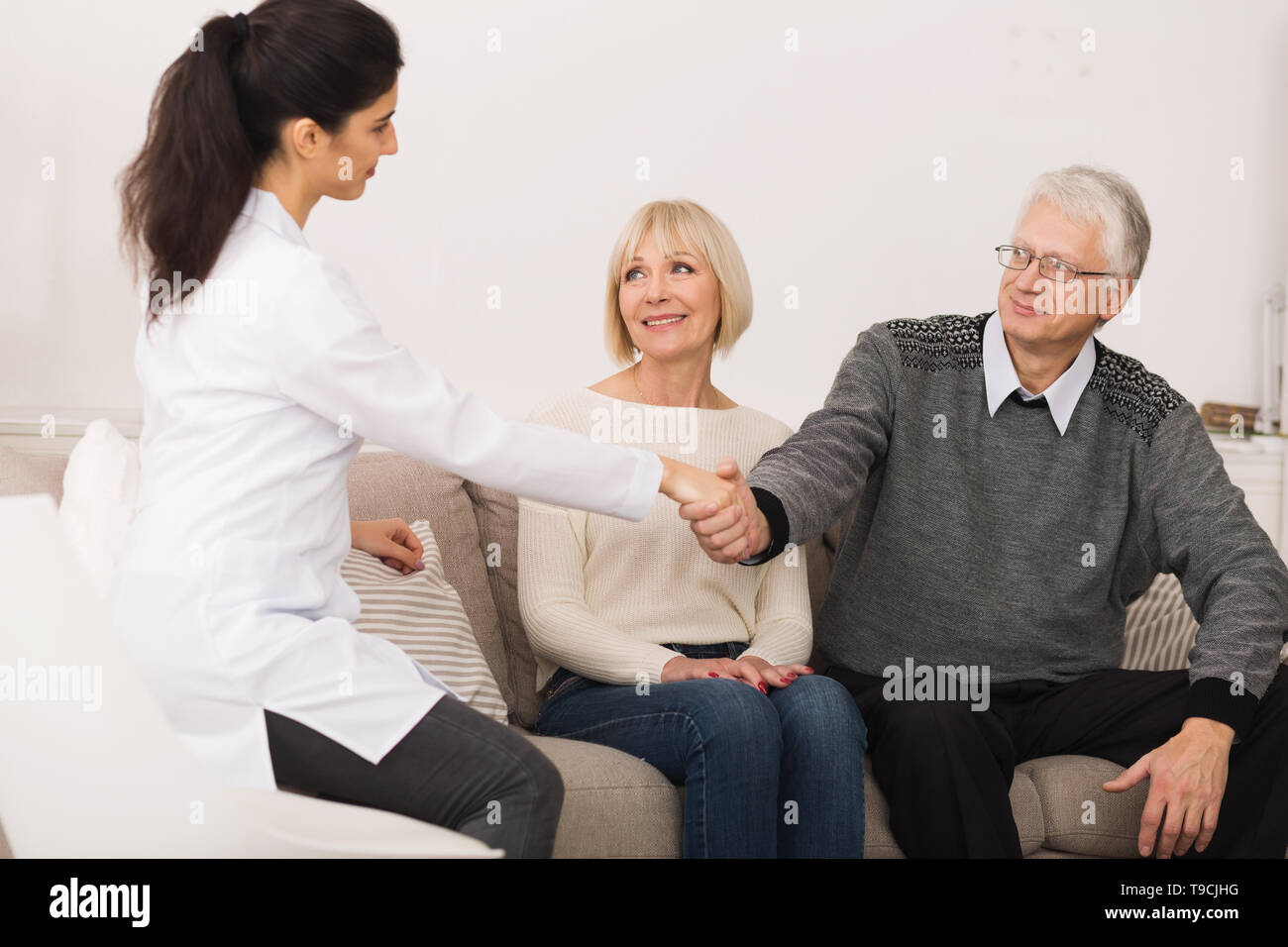 Mature Couple Welcoming Nurse During Home Visit - Stock Image