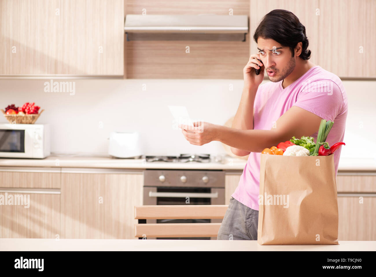 Young handsome man with vegetables in the kitchen - Stock Image