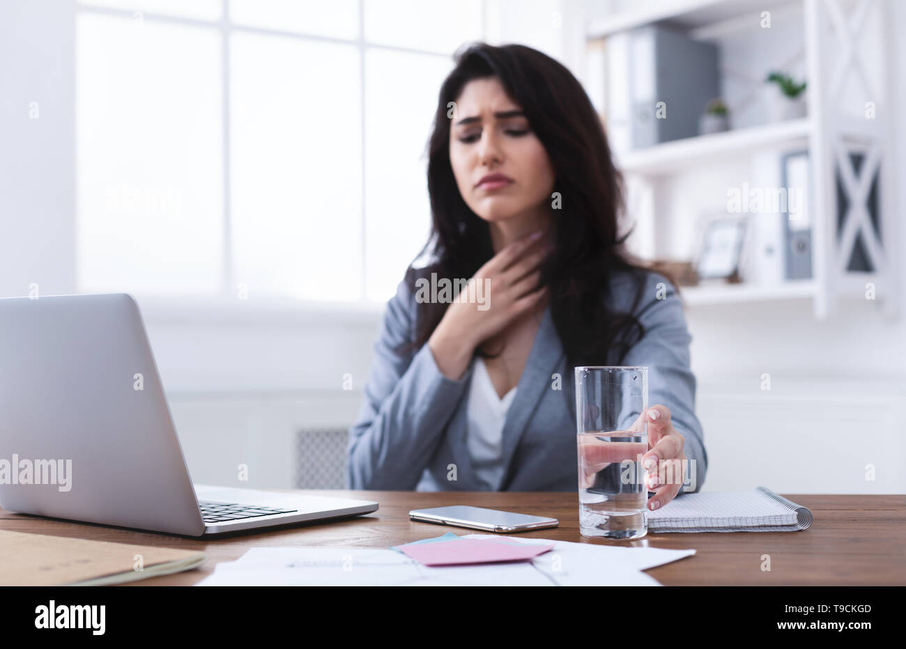 Sick Businesswoman With Sore Throat Trying To Work - Stock Image
