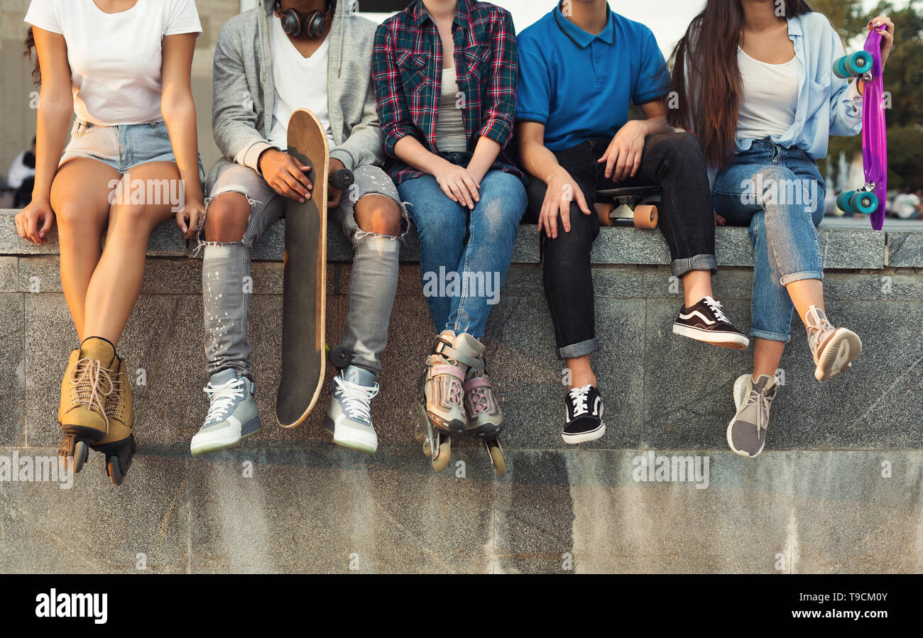 Active diverse friends sitting in urban skatepark with skateboards - Stock Image