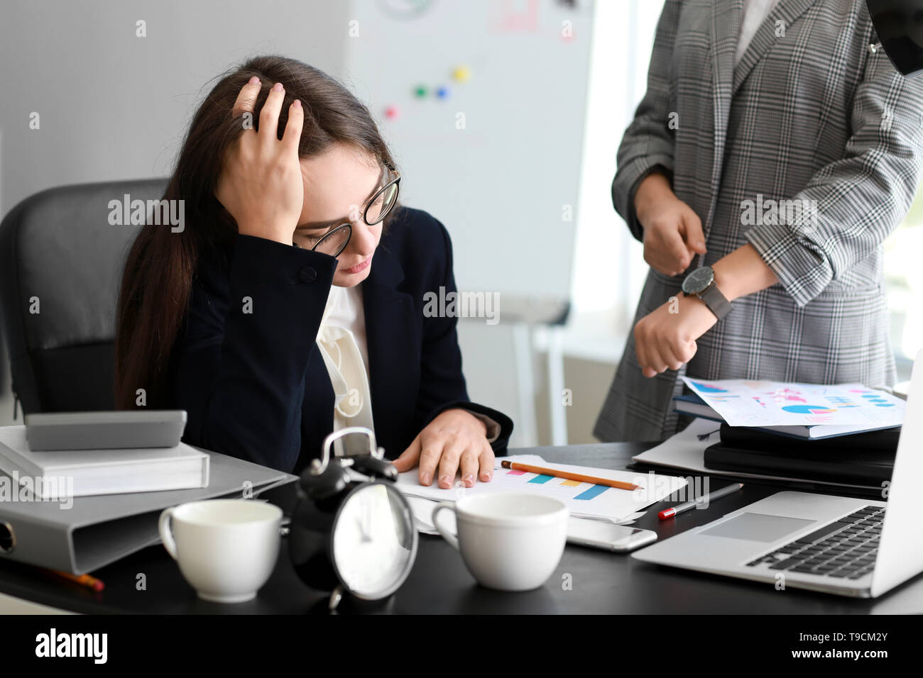 Boss reminding young woman of duration in office - Stock Image