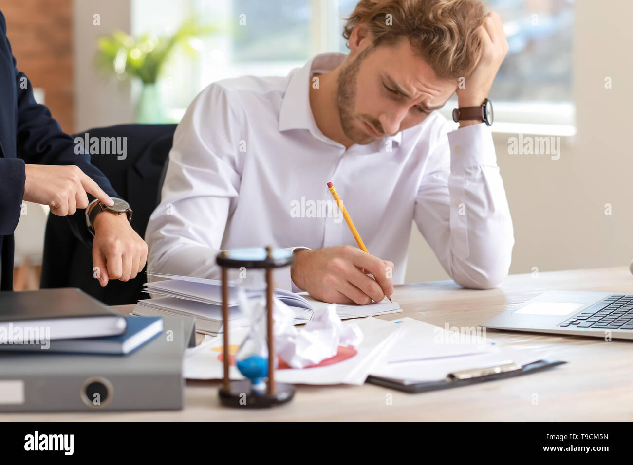 Boss reminding young man of duration in office - Stock Image