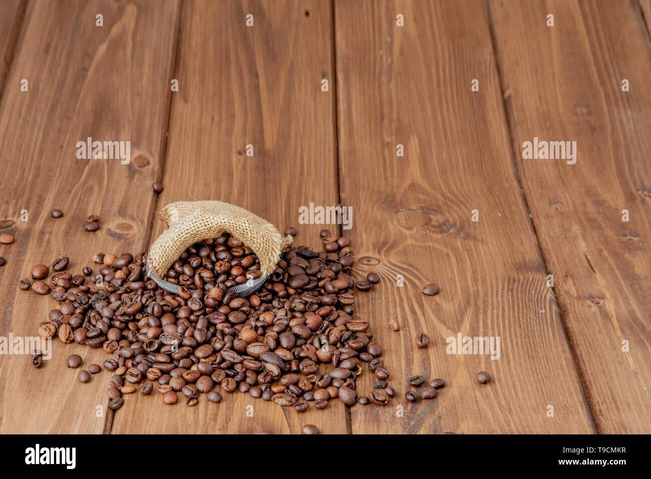 Fresh roasted coffee beans falling out the sack on the wooden surface. Brown coffee beans scattered from bag on the table. - Stock Image