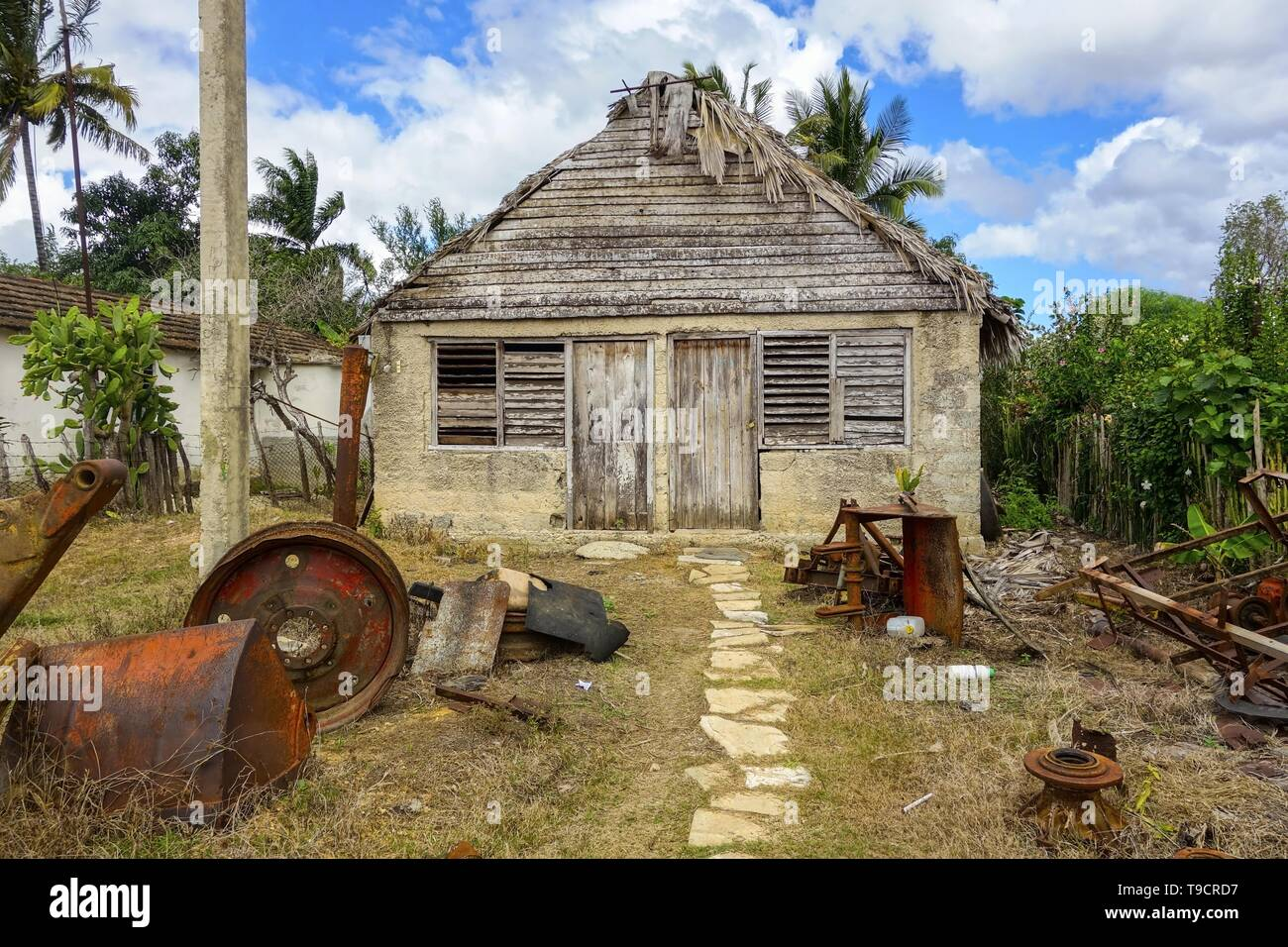 Vintage Old Farm House Building Exterior and Front Yard with Rusted Machinery Pieces in Traditional Cuban Countryside Rural Village Stock Photo