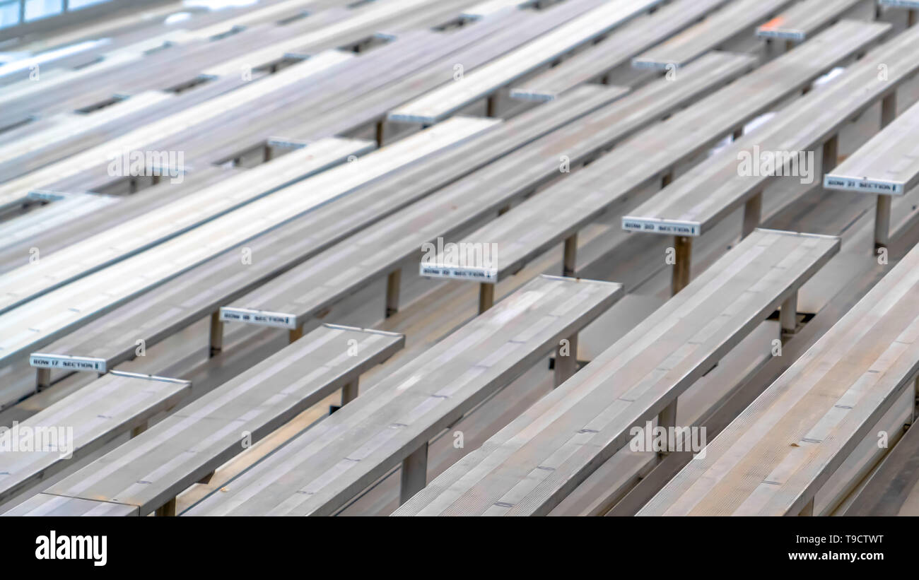 Clear Panorama Close up of tiered rows of benches at a sports field viewed on a sunny day. - Stock Image