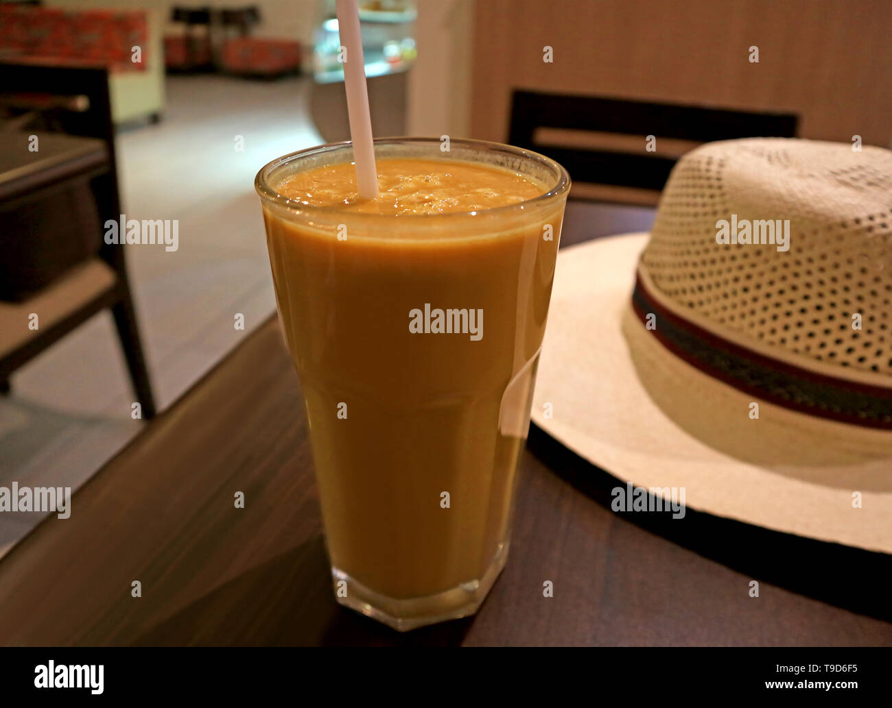 huge discount 4e394 50f82 Glass of Healthy Creamy Lucuma Fruit Juice Served on Wooden Table with a  White Straw Hat