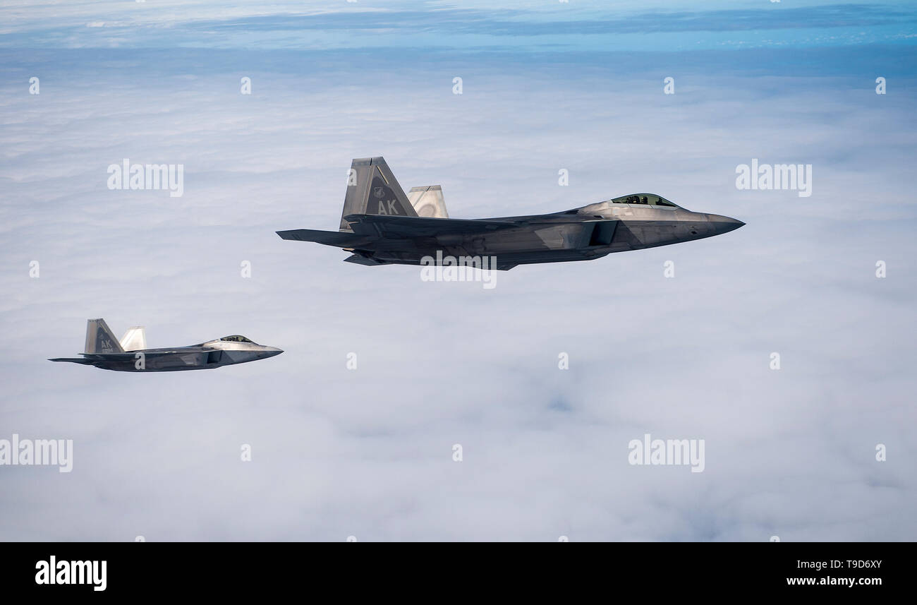U.S. Air Force F-22 Raptors fly over Alaska during Northern Edge, May 14, 2019 at Joint Base Elmendorf-Richardson, Alaska. Northern Edge provides effective, capabilities-centered joint forces, ready for deployment world-wide and enables real-world proficiency in detection, identification and tracking of units at sea, in the air and on land and respond to multiple crises in the Indo-Pacific region. (U.S. Air Force photo by Master Sgt. Nathan Lipscomb) - Stock Image