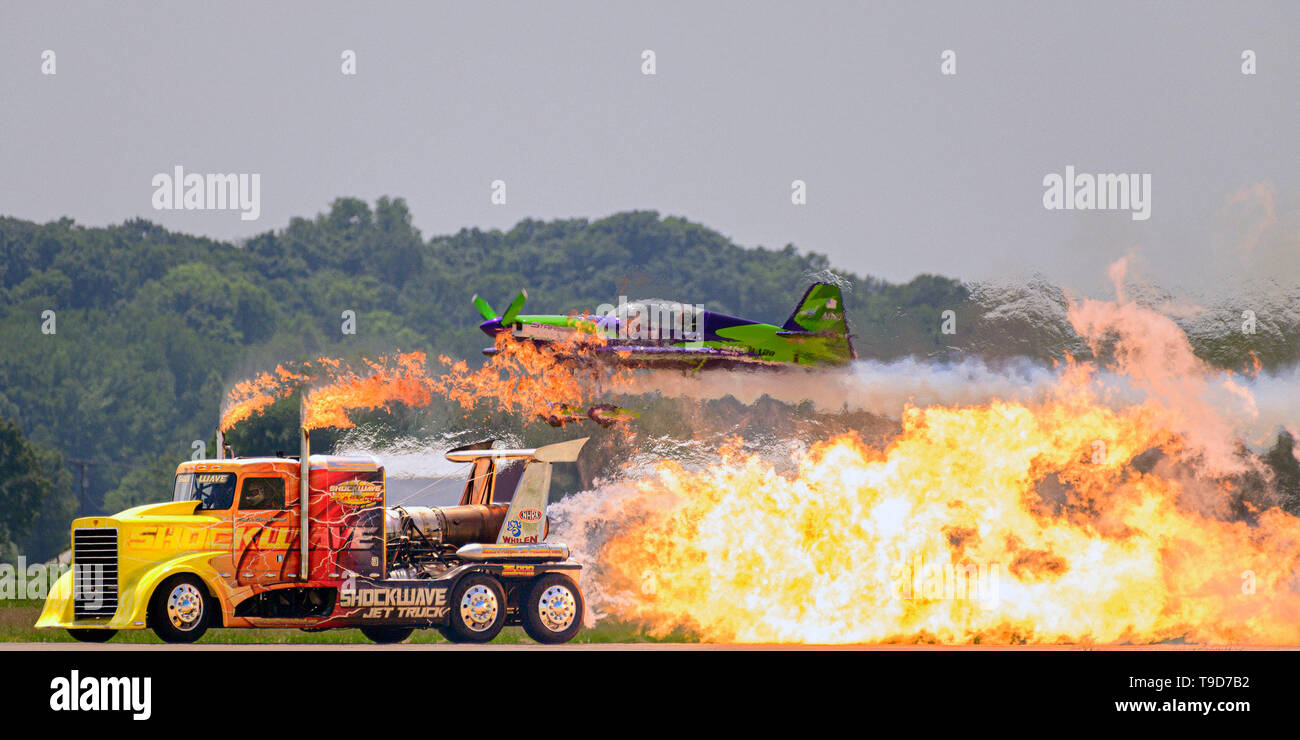 """190517-N-JH293-1048  CAPE GIRARDEAU, Mo. (May 17, 2019) The """"Shockwave"""" jet truck races an MX2 aircraft piloted by Gard Ward during the 2019 Cape Girardeau Air Festival """"Friends and Family Day"""", May 17, 2019. The festival is a pastime in the U.S. Midwest, which has been welcoming thousands of aviation enthusiasts to the area since 1995. This year's event features the U.S. Navy flight demonstration squadron, the Blue Angels, and more. (U.S. Navy photo by Mass Communication Specialist 1st Class Chris Williamson/Released) - Stock Image"""