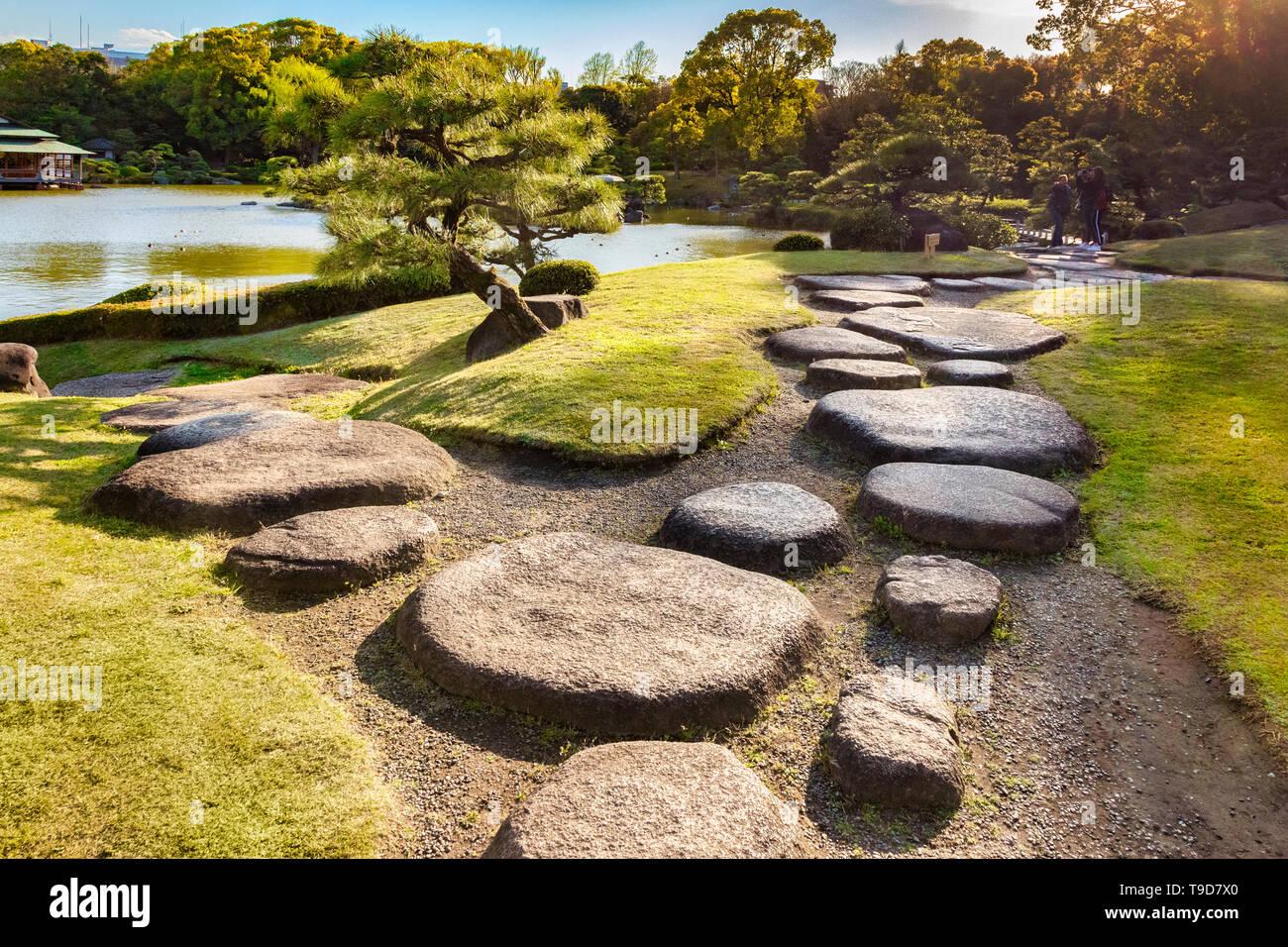 9 April 2019: Tokyo, Japan - Kiyosumi Garden, stepping stones beside the lake. Flare as sun sets on top right. Stock Photo