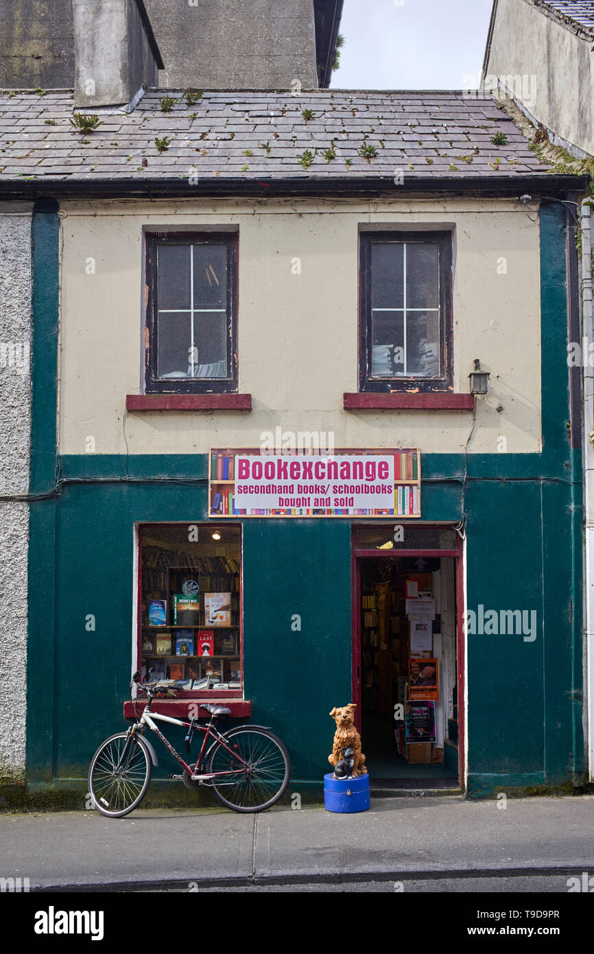 Secondhand bookshop with animal collecting box and bike outside in Galway, Ireland - Stock Image